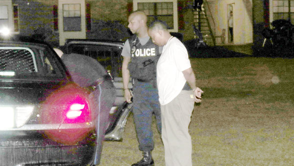 Richard escorted handcuffed to police care by EBPD Officer Russell Clausell after being arrested Monday evening.