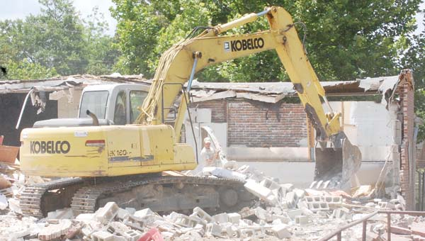 City workers use heavy equipment to tear down the walls of old BMS classrooms Tuesday.