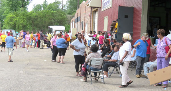 Hundreds of people wait in line to receive food distributed by New Beginnings Worship Center members and volunteers.