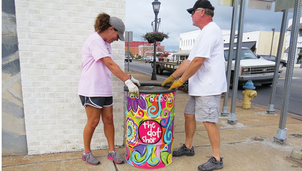 Mary Brown, left, and Eric Douglas work to place more than a dozen barrels around town as part of the Brewton Reborn program.