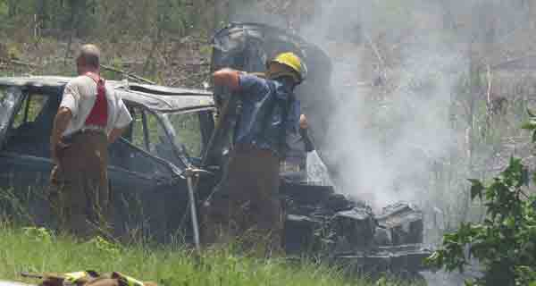 Firefighters with the Dixonville Volunteer Fire Department work to extinguish the blaze that engulfed the van Jessica Day was driving Monday.