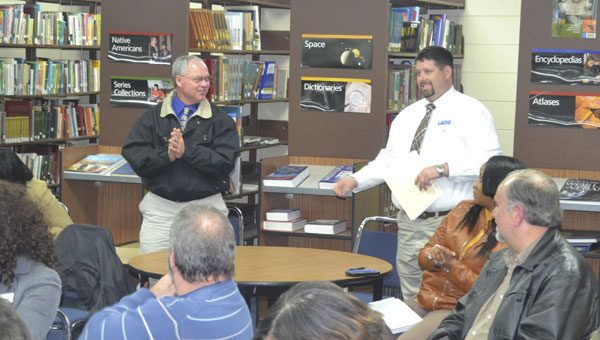 Escambia County High School principal Dennis Fuqua, right, introduces new ECHS football coach Royce Young, left, during Thursday's Escambia County Board of Education meeting at the ECHS library.| Photo by Justin Schuver