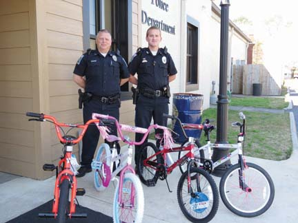 BPD officers Shane Brannock and Chris Byrd pose with the bounty for this week's bike rodeo. Four lucky children – two boys, two girls – will win these bicycles.