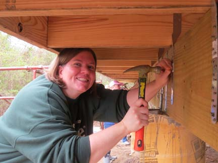 Rebecca Mollenbrink puts her first nail in her new Habitat for Humanity home Saturday.