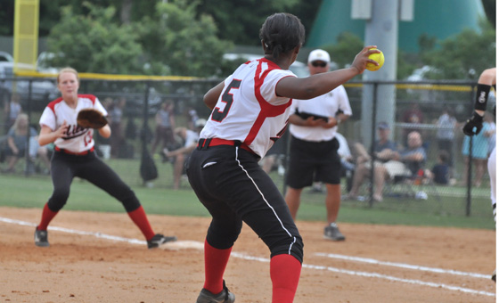 TRM Lady Tiger senior pitcher Moriah Brundidge, right, throws to other senior Abbi Roberts as she covers first on a bunt against Straughn Saturday at the South Regionals in Gulf Shores.