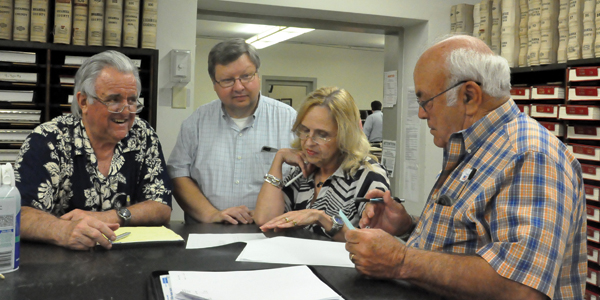 Everett Price, Chuck Johns, Carol Ellington and Terry Clark study print out of box totals Tuesday.