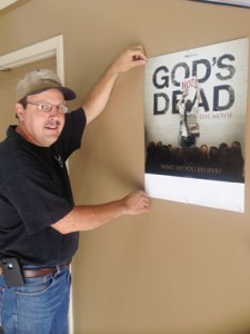 Pastor Bo Bell hangs a sign for this Friday's movie. Admission is $3 per person. Concessions will be available. Doors open at 5 p.m. Movie begins at 7 p.m.