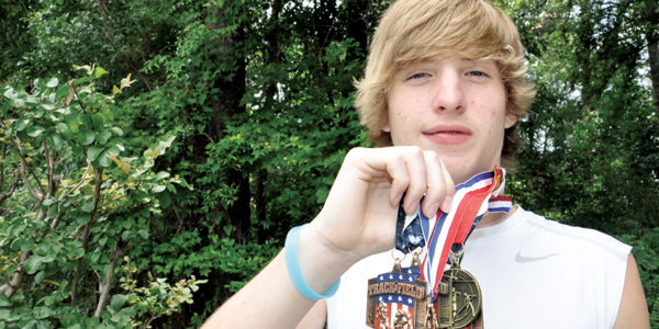Joshua Gunter shows off the grouping of medals he's brought home after recent track meets.