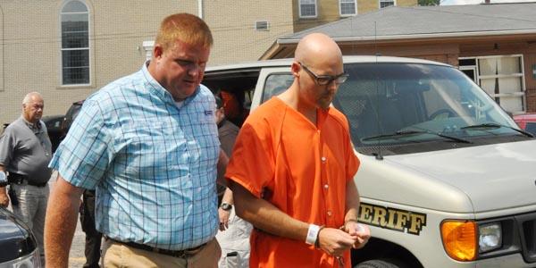 Brewton Police Chief Monte McGougin escorts former TRM band teacher Jeffery Lance Ganious into court Friday for a bond hearing.
