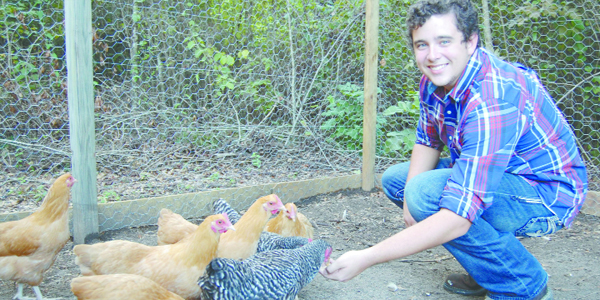 Stephanie Nelson | Brewton Standard Connor Rush shows off his chickens Monday in his Appleton Road chick coop. Below:Rush feeds the chicken by hand.