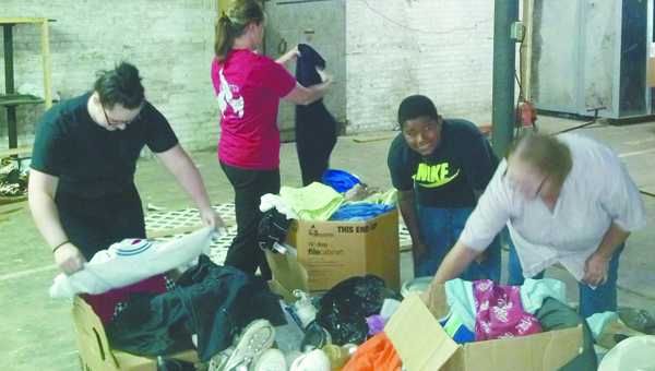 Courtesy photo Volunteers work Tuesday to sort clothes for the new Compassion for Brewton thrift store.