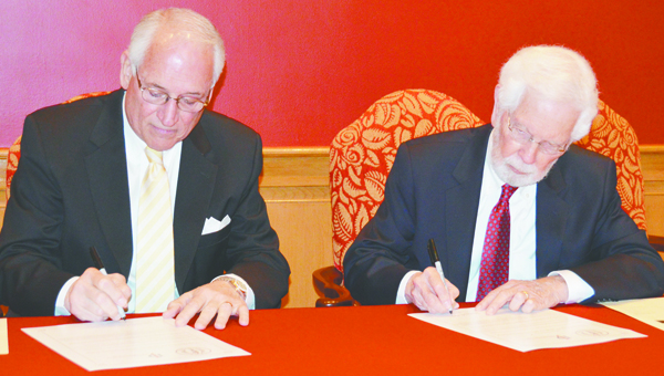 Stephanie Nelson | Brewton Standard Dr. Jack Hawkins Jr., Chancellor of Troy University, and Dr. William Blow, interim president of Jefferson Davis Community College, sign the agreement.  between the two schools that will enable transfer students to complete their associate's degree while pursuing their bachelor's degree.