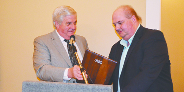 Local attorney Ed Hines presents Roger Chapman with the hoor.