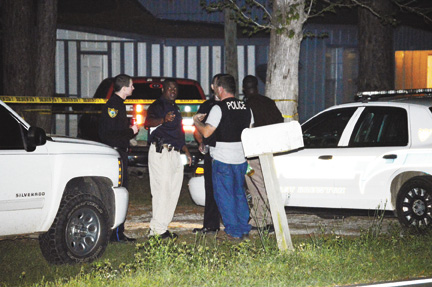 Members of the East Brewton Police Department stand outside the crime scene Tuesday night.