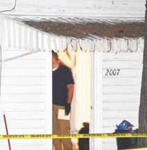 An investigator pauses in the home's doorway as the scene is processed.