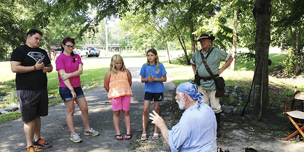 Kale Evans, Audrey Hill and Mary and Annabelle Gunn listen as re-enactor Lee Lehman discusses life during the time of the Battle of Burnt Corn Creek Saturday.
