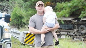 Taylor White holds his son, Jayce, after helping pull a woman to safety following a crash on U.S. Hwy. 29.