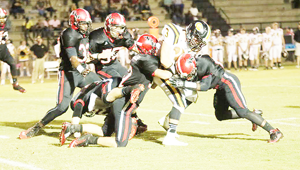 Miller players use teamwork to bring down a Geneva    runner in Friday night's homecoming game. Miller's defense held Geneva's offense to 242 total yards in the game.