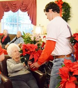 Meadow's resident Wilma Lambert receives a poinsettia from JoJo Booker.