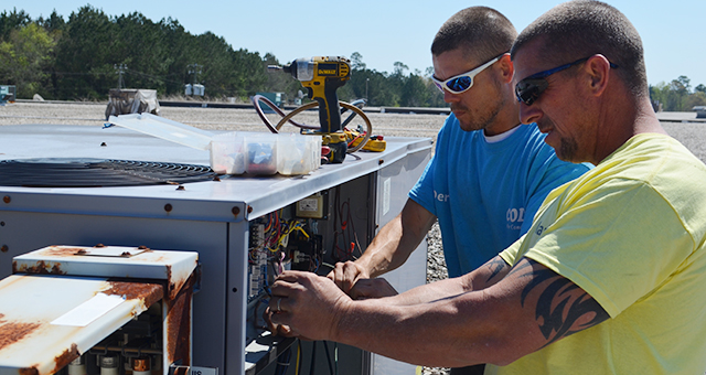 Corey Williams | The Brewton Standard Coley Air Conditioning mechanics Derek Harrison and Mark Dorriety work to replace burnt out wires on a package AC unit.