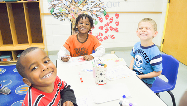 Stephanie Nelson | The Brewton Standard These cheesy cuties are among those currently enrolled at Brewton Head Start. Here, the trio works on their coloring.