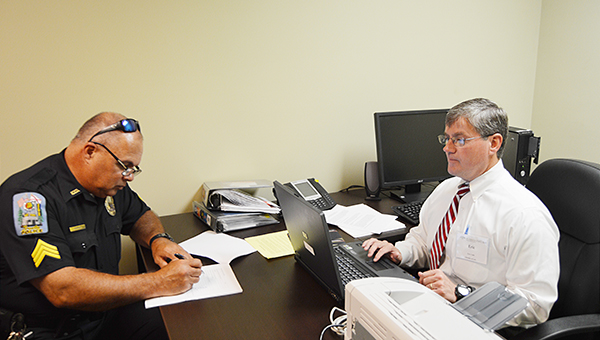 Stephanie Nelson | The Brewton Standard Brewton Police Officer Hal Parker fills out paperwork for Eric Coale as part of the 'Wills for Heroes' project.