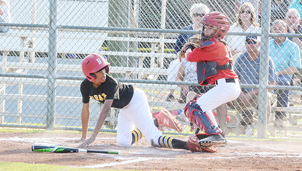 Corey Williams | The Brewton Standard Trent Cooper of the Pirates slides home against the Reds.