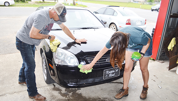 Corey Williams | The Brewton Standard Blake and Whitney Bullard work on the headlights. The Bullards began the business 10 years ago and have worked in Colorado and Texas before setting up shop in Brewton.