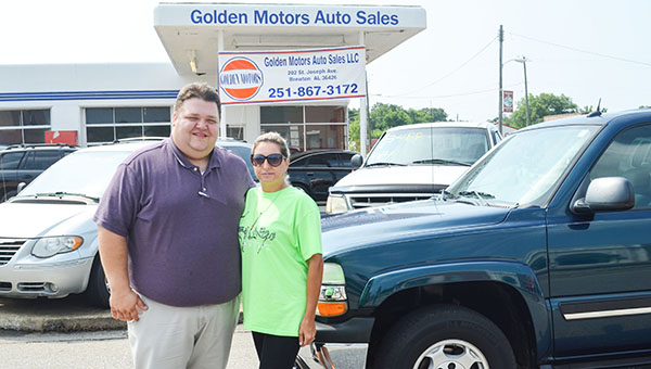 Corey Williams | The Brewton Standard Golden Motors Auto Sales owner Luke Golden with one of his customers, Beverly Brown Lucas. Golden sold Lucas the 2005 Bremuda Blue Chevrolet Tahoe pictured in the background.