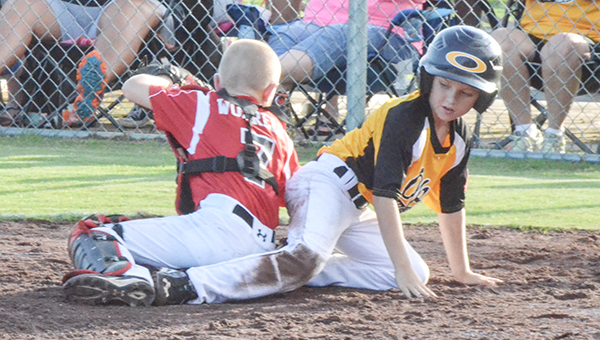 Corey Williams | The Brewton Standard An Opp baserunner slides in safe as Brewton's Emerson Worrell attempts to tag him out in game one. Brewton won game one in extra innings, 10-9.