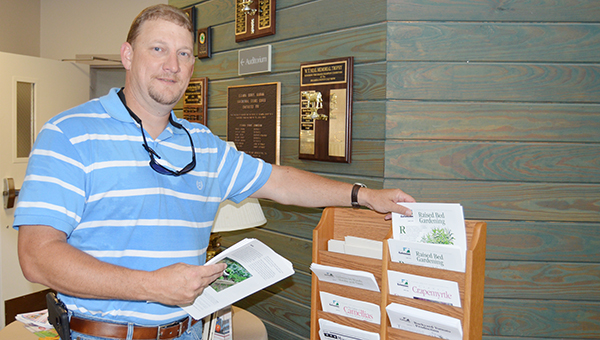 Stephanie Nelson | The Brewton Standard Anthony Wiggins, new Escambia County Extension agent, stocks the front lobby of the office on Ag Science Drive Tuesday.