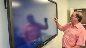 Corey Williams | The Brewton Standard Escambia County Schools Superintendent John J. Knott tests out the ClearTouch Interactive Board. All classrooms are equipped with the smart board.