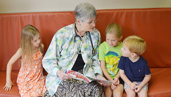 Corey Williams | The Brewton Standard Dr. Marsha Raulerson reads a story of Clifford the Big Red Dog to Kate Kelley, Presley Kelly and Mac Newby.