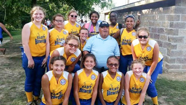 Courtesy photo The 12U softball team snaps a picture with umpire Sam Gonzales after he gives them some great words of advice. Gonzales had been officiating for 54 years for basketball, baseball and served as a referee for Bear Bryant. The regional tournament was his last tournament.