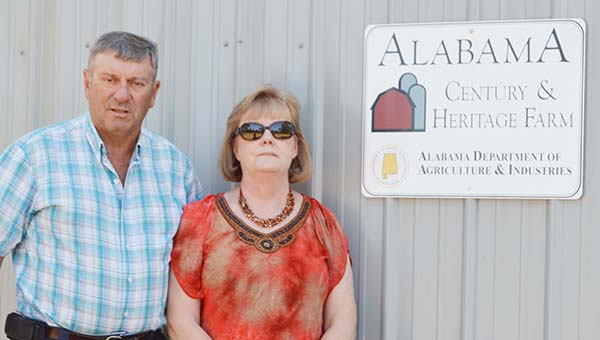 Lydia Grimes | The Brewton Standard Jerry and Theresa Bell stand in front of barn next to their Alabama Century and Heritage Farm plaque presented to them by the Alabama Department of Agriculture and Industries.