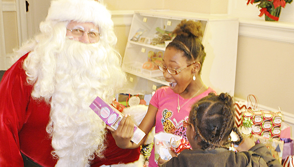 Stephanie Snodgrass | The Brewton Standard Santa watches as Zykeria Samuel (hot pink) and  Neveah McCall (black jacket) opens their presents, which were provided in part by the Escambia County Drug Court participants