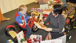 Stephanie Snodgrass | The Brewton Standard Josiah Baynard (boy on bike) and mom, Deliah, go through the stack of presents left for him on Friday.