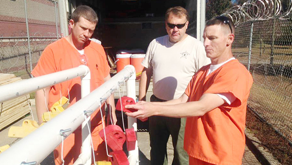 Stephanie Snodgrass | The Brewton Standard Escambia County Detention Center inmates hang the dyed wooden cars to dry as part of their project to provide for needy children.